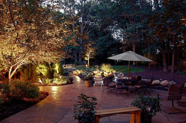 Landscape lighting illuminating an outdoor seating area that is paved with stone pavers.