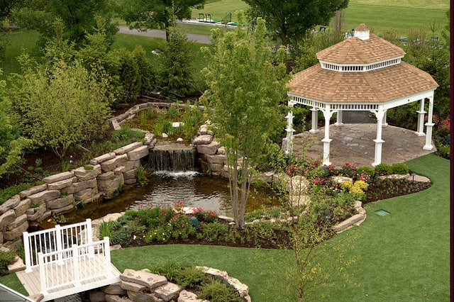 A landscape pond made out of stone in a grassy backyard adjacent to a white gazebo.