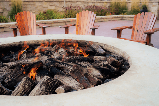 A close up of an outdoor gas fire pit surrounded by wooden Adirondack chairs