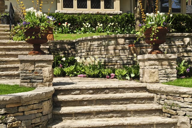 stairs and retaining walls made our natural tan stone in a yard with lush landscaping featuring colorful flowers.