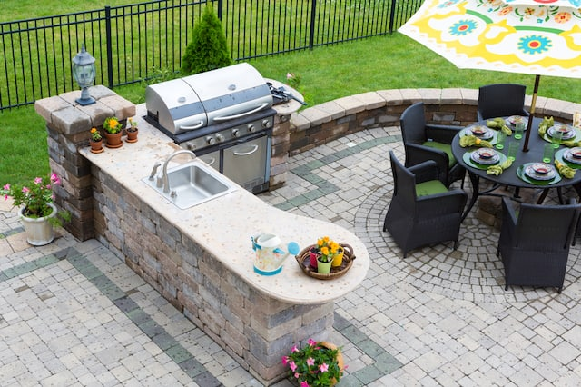 An outdoor kitchen with pavers, an outdoor gill, a bar with a sink, and a round table with chairs and an umbrella.