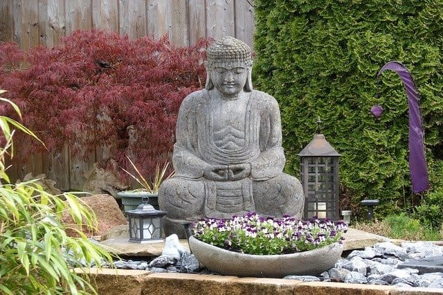A grey stone statue of Buddha sitting in a rock garden with a Japanese maple tree in the background and other plants nearby.  Japanese garden and zen garden landscaping ideas.